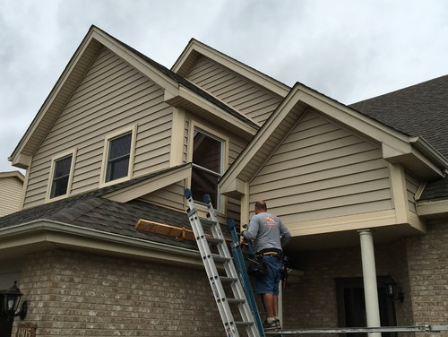 Roofing worker climbs ladder to replace roof after wind damage