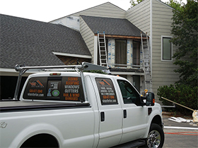 Roofing contractors car near vinyl siding house in Naperville