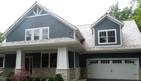 Charming exterior transformation project photo after HardiePlank lap siding installation, roof repair and window replacement  in Northbrook