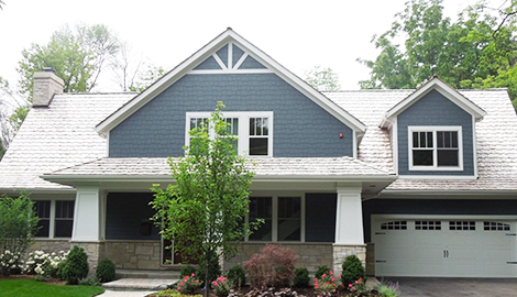 Charming exterior transformation project photo after HardiePlank lap siding installation, shake roof and window installation in Northbrook
